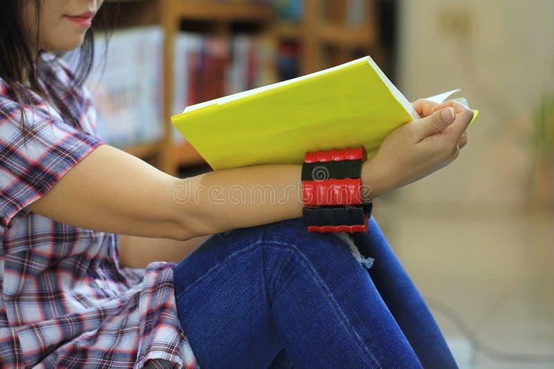 妇女看书在图书馆屋子和书架背景,教育概念里 免版税库存图片