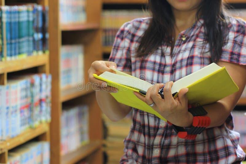 妇女看书在图书馆屋子和书架背景,教育概念里 免版税库存照片