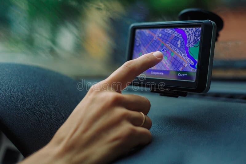 妇女看在汽车的一个GPS导航员 库存图片