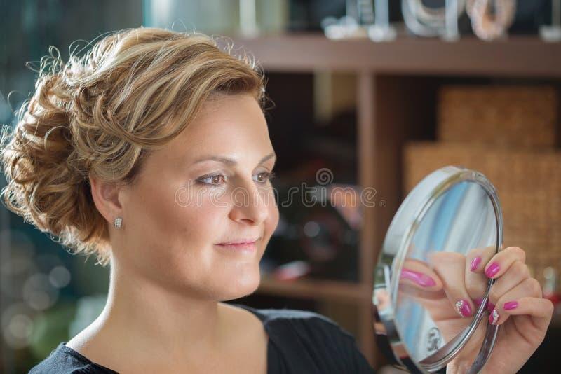 妇女看她自己在镜子 免版税图库摄影