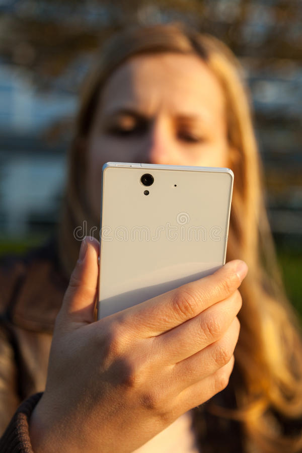 妇女看看白色智能手机 库存图片