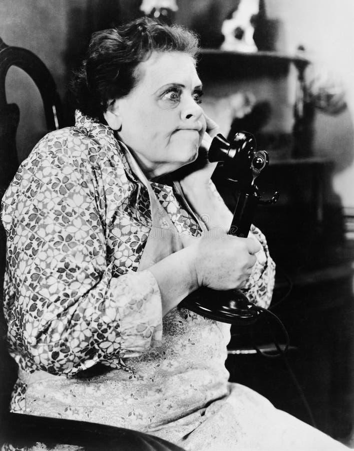 妇女看起来恼怒和谈话在电话(所有人被描述不更长生存,并且庄园不存在 供应商warrantie 免版税库存图片