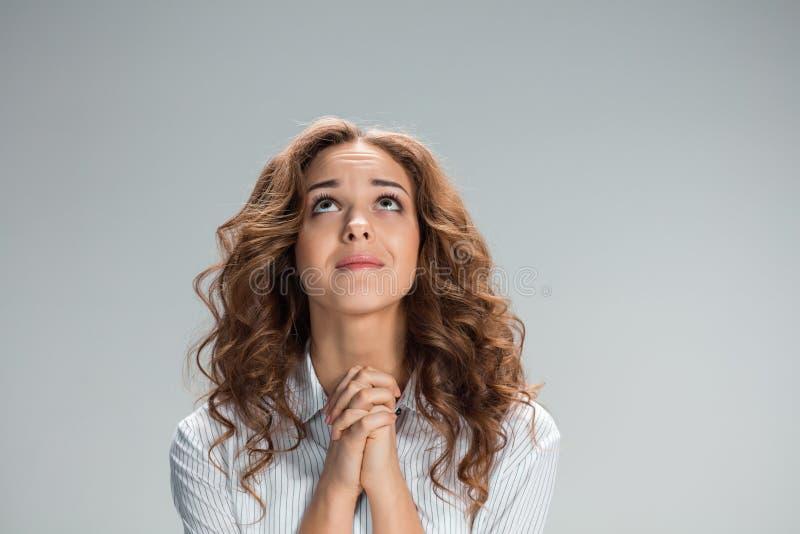 妇女看起来祈求在灰色背景 库存图片