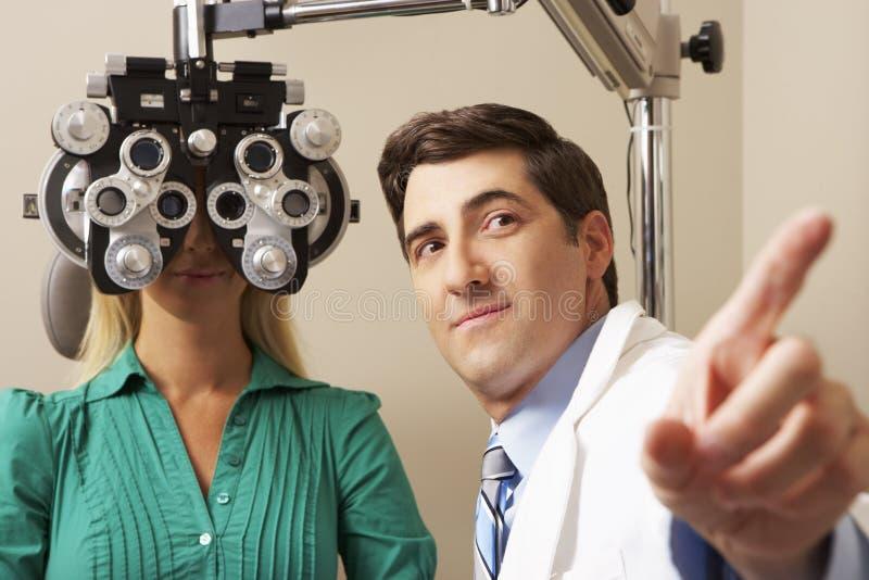 给妇女眼睛测试的手术的眼镜师 库存图片
