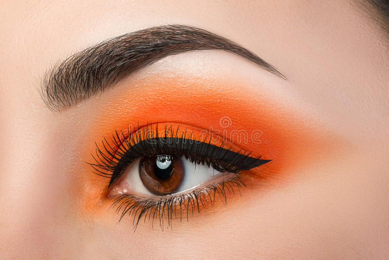 妇女眼睛特写镜头与美丽的橙色smokey的注视 图库摄影