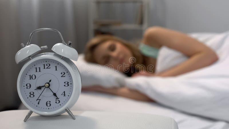 妇女睡过头在早晨的,敲响在床,每日惯例附近的闹钟 图库摄影