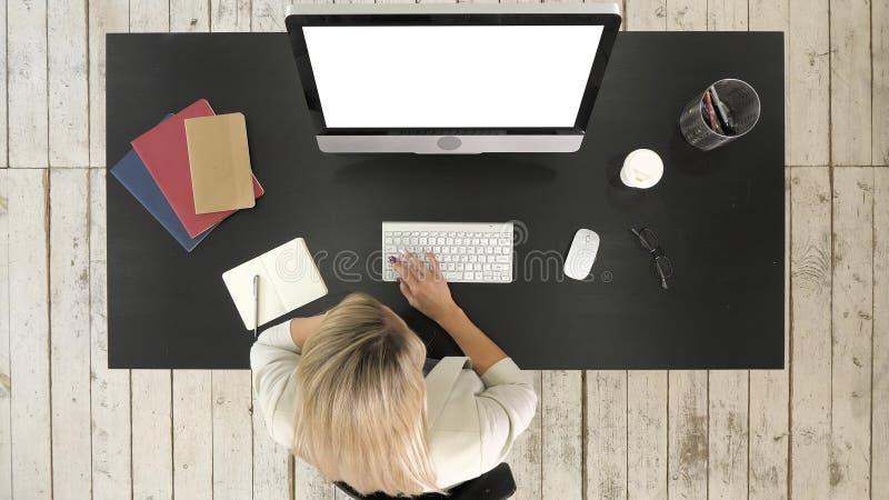 妇女研究计算机和谈话在电话 空白显示 库存图片