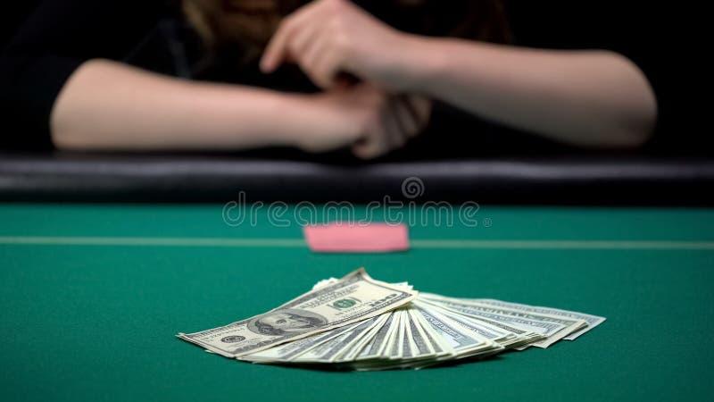 妇女确信对她的把美元放的卡片在赌博娱乐场桌上,浪费金钱 免版税库存图片