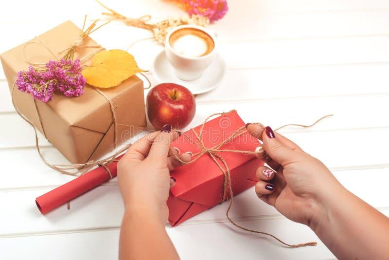 妇女礼物为秋天假日、生日或者感恩天做准备 苹果秋天对光检查袋装花瓶的构成干燥叶子 手工制造被包裹的礼物盒,秋天l 免版税图库摄影