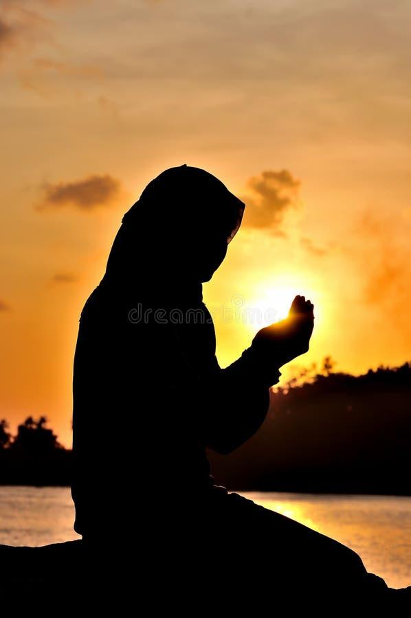 妇女祈祷的剪影 免版税库存照片