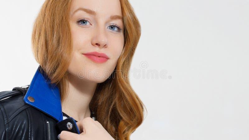 妇女秀丽力量 关闭红发女孩面孔,在白色背景的皮夹克 皮肤护理,蓝眼睛 免版税库存照片