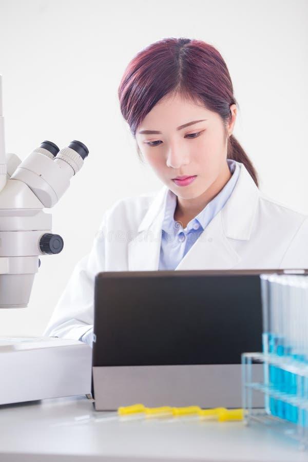妇女科学家用途显微镜 免版税库存图片