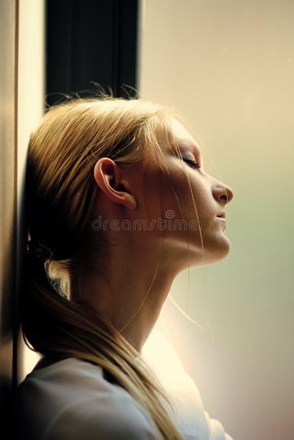 妇女秘密 有金发马尾辫的妇女放松在窗口,白日梦 梦想,白日梦,凝思 健康和 图库摄影