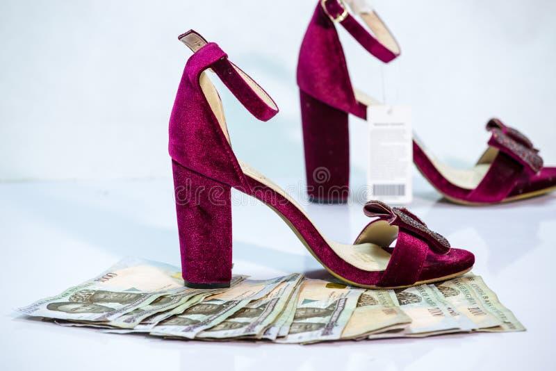 妇女穿上鞋子与捆绑奈拉注意当地货币现金 库存图片
