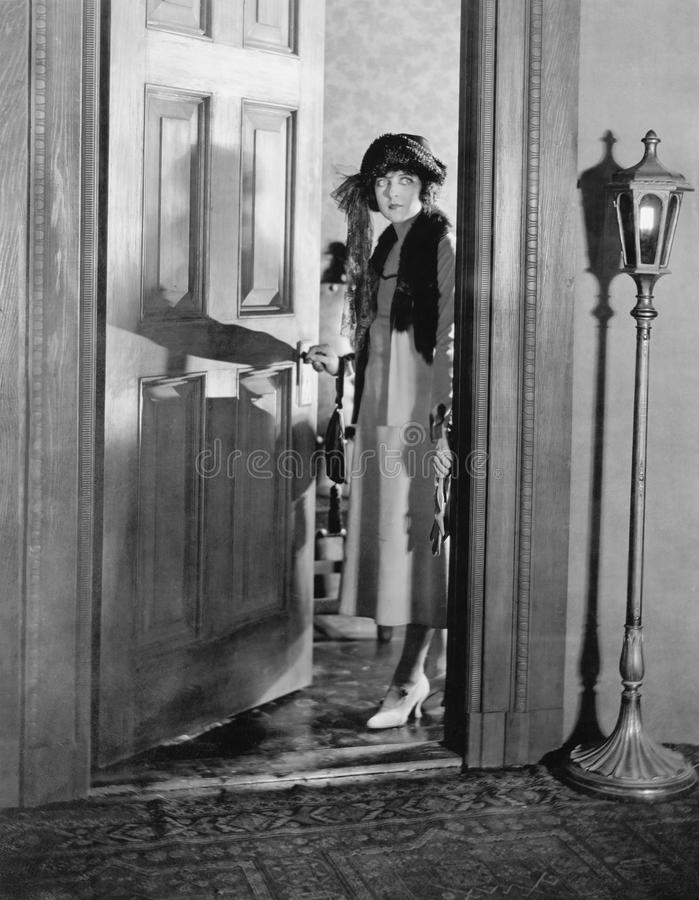 妇女穿戴了站起来在门道入口(所有人被描述不更长生存,并且庄园不存在 供应商保单Th 免版税库存照片