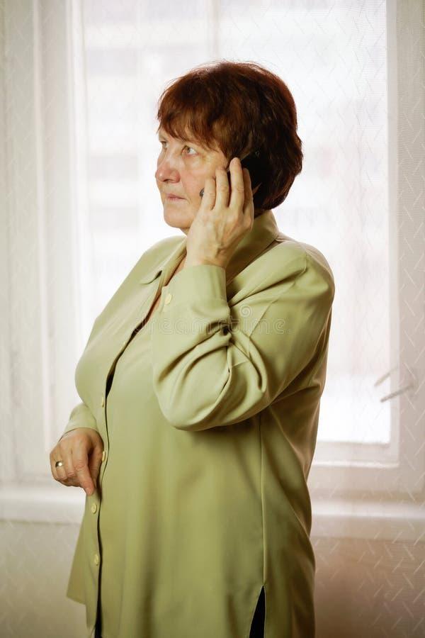 妇女站立和谈话在电话,看与边 库存图片