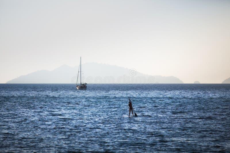 妇女站立在原始海的桨搭乘在酸值Lipe 免版税库存图片