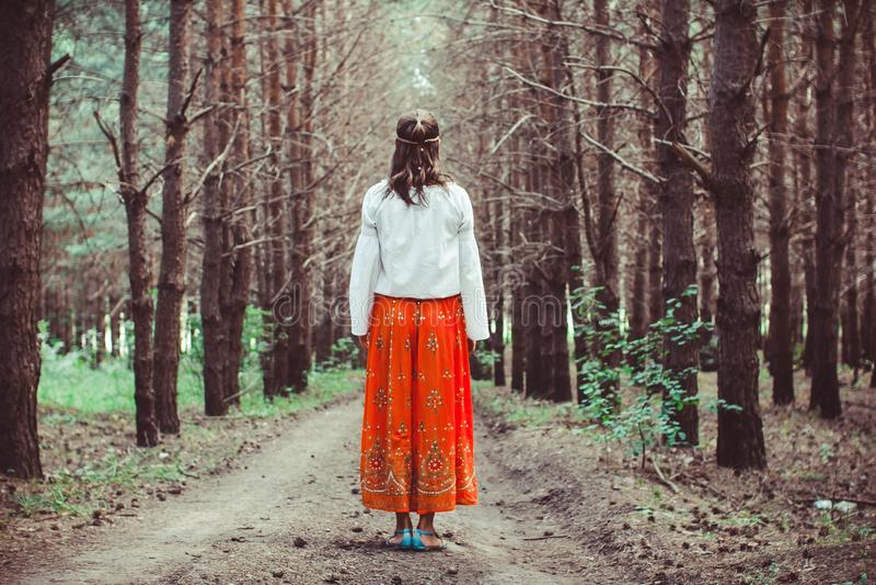 妇女站立在树之间 免版税库存照片