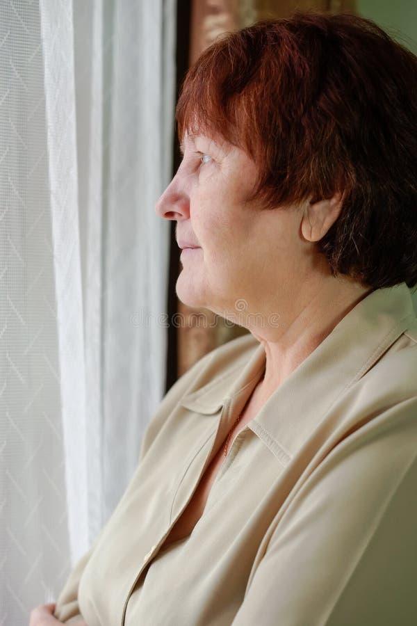 妇女站立在窗口,看他,微笑 库存图片