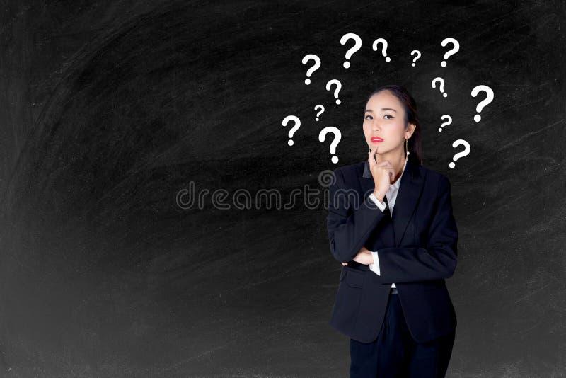 妇女站立有问号黑板背景 免版税库存照片