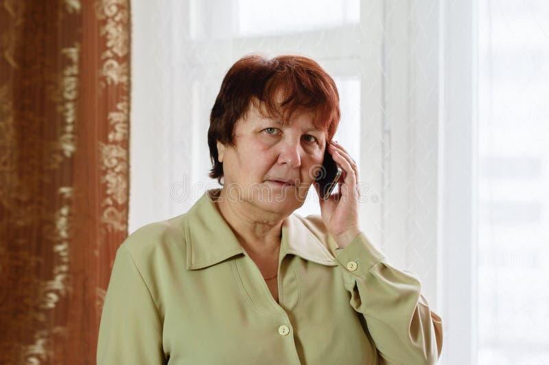 妇女站立,看照相机和谈话在电话 免版税库存照片