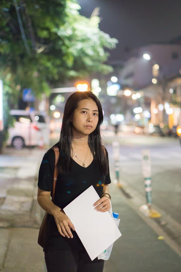 妇女等待的出租汽车或公共汽车在街道上 免版税库存图片