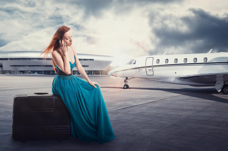 妇女等待的飞行离开在机场谈话在电话 免版税库存照片