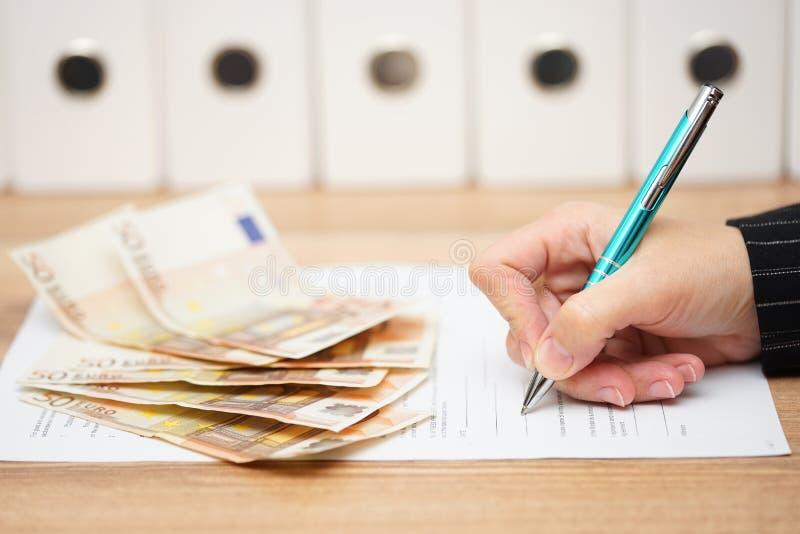 妇女签合同得到很多金钱 免版税库存照片