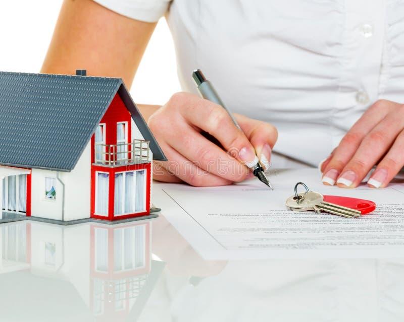 妇女签署房子的协议 免版税库存图片