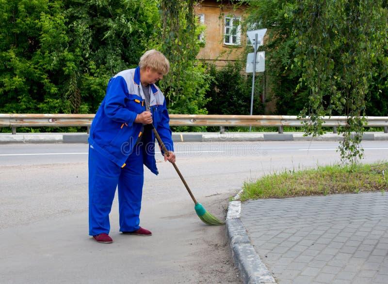 妇女管理员清扫街道 库存图片