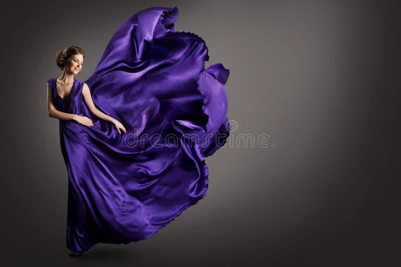 妇女紫色礼服,在长的丝绸褂子挥动的布料的时装模特儿在风,飞行的振翼的织品的幻想女孩 库存照片