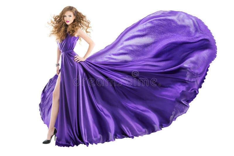 妇女紫色礼服,在长的挥动的振翼的褂子的时装模特儿 免版税图库摄影
