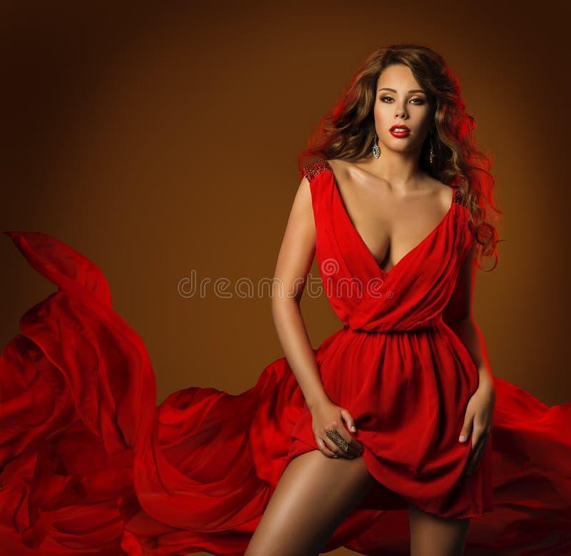 妇女红色礼服,时装模特儿姿势飞行织品布料 免版税库存图片