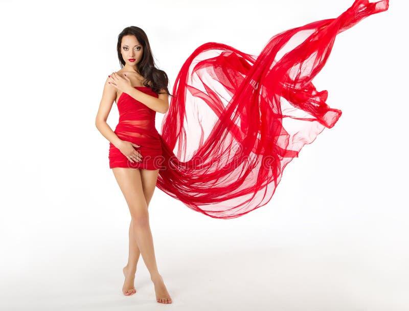 妇女红色飞行挥动的礼服,白色 库存图片