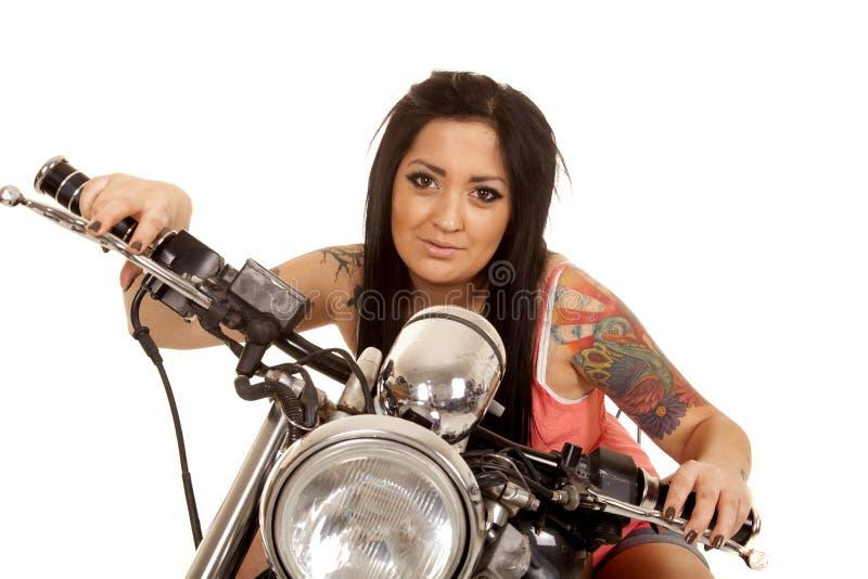 妇女纹身花刺桃红色衬衣摩托车微笑 免版税库存图片