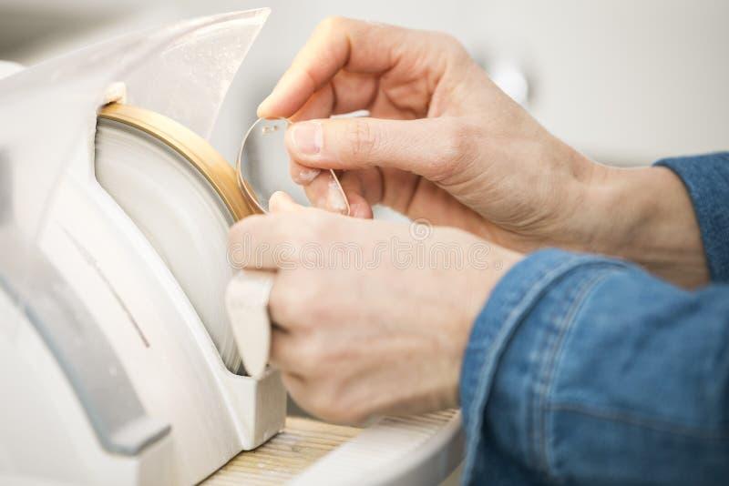 妇女细磨刀石镜片的边缘 免版税图库摄影