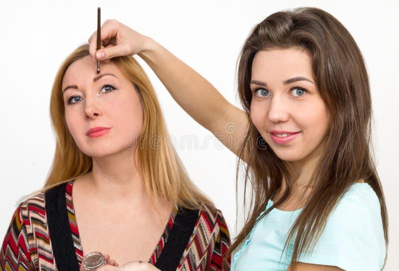 妇女绘了在美容院的眼眉 库存图片