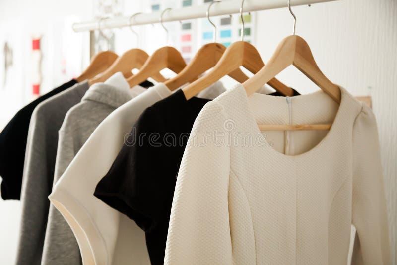 妇女给垂悬在挂衣架衣物路轨穿衣,时尚设计 库存照片
