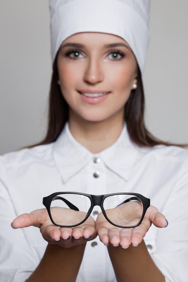 妇女给玻璃的医生眼医接近的画象  免版税库存图片