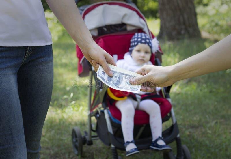 妇女给金钱美元孩子的一个人,交易对于儿童 图库摄影