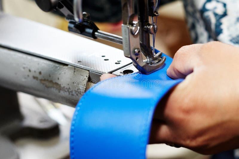 妇女缝合与一台特别缝纫机的皮革带皮革的,用于提包/鞋子的生产 免版税库存照片