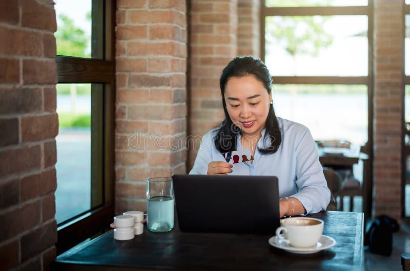 妇女网络购物和食用咖啡 图库摄影
