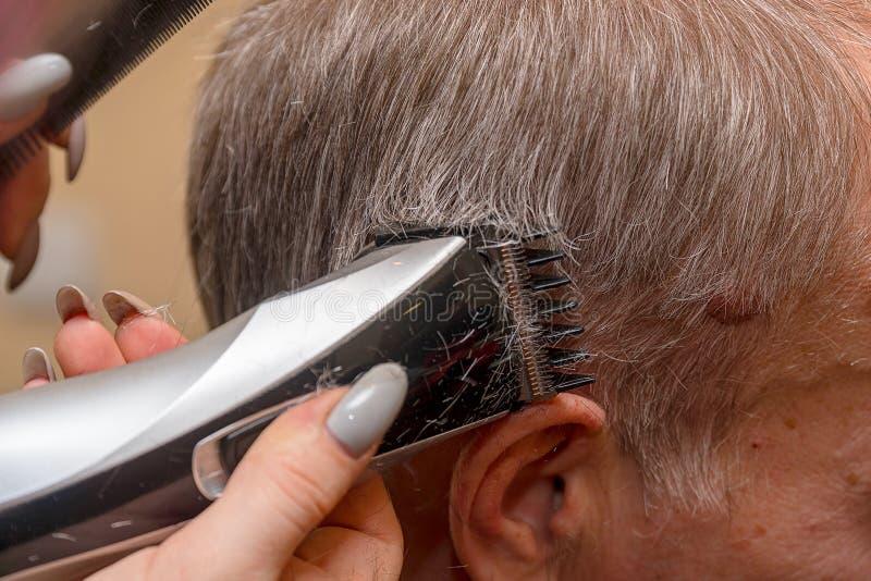 妇女美发师剪有电推子整理者的人的头发 免版税库存图片