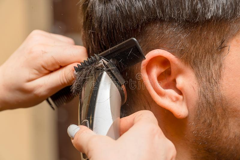 妇女美发师剪有电推子整理者的人的头发 免版税图库摄影