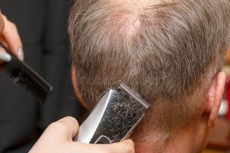 妇女美发师剪有电推子整理者的人的头发 免版税库存照片