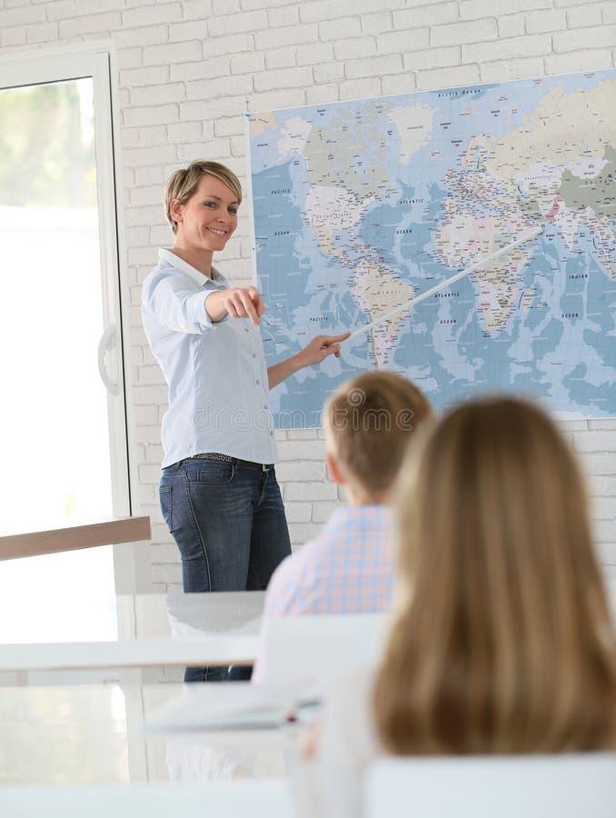 妇女老师在教室在学校 免版税库存图片