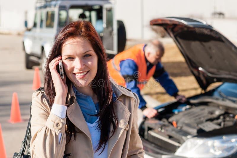 妇女联系在移动电话在汽车细分以后 免版税库存图片