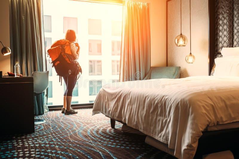 妇女背包徒步旅行者旅客逗留在优质旅馆客房 免版税库存照片