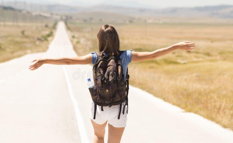 妇女背包徒步旅行者走在路的和胳膊打开 库存照片