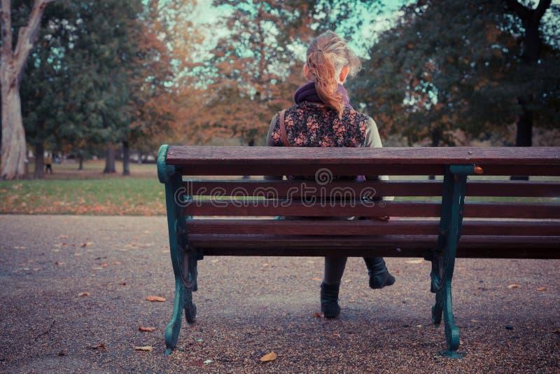 妇女背面图公园长椅的 免版税图库摄影